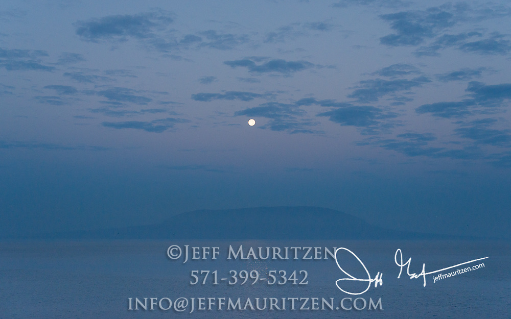 Full moon over Fernandina island, part of the Galapagos islands.