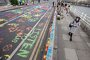 UNITED KINGDOM, London: 16 April 2019 <br /> A member of public walks past graffiti written by Extinction Rebellion protesters as the protests continue on Waterloo Bridge today. It is the second day of protests that have appeared in five locations across the city. Police officers have made more than 120 arrests in the last 24 hours.<br /> Rick Findler / Story Picture Agency