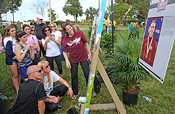 Sitting on the ground, parents of slain Marjory Stoneman Douglas High School student Nicholas Dworet, Mitch and Annika Dworet, look at an art piece to celebrate their son at the Parkland Hearts Art Project at Trails End Park in Parkland, FL, USA, Thursday, February, 14, 2019. Photo by Charles Trainor Jr./Miami Herald/TNS/ABACAPRESS.COM