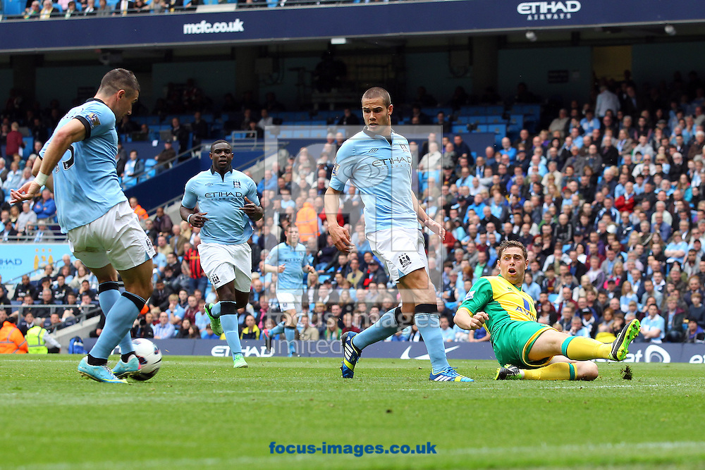 Picture by Paul Chesterton/Focus Images Ltd +44 7904 640267.Grant Holt of Norwich narrowly misses the ball as it is ccrossed during the Barclays Premier League match at The Etihad Stadium, Manchester.