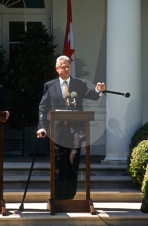 President Bill Clinton points with his crutch during a joint press conference with Canadian Prime Minister Jean Chrétien in the Rose Garden April 8, 1997 in the White House.