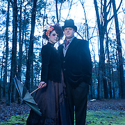 A Caucasian couple chose a Tim Burton theme for their engagement portrait session. The woman wore a vintage black dress and the man wore a suit and top hat. She is holding a vintage umbrella and had her hair and make-up done similar to the style seen in Tim Burton films.