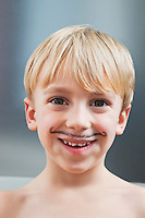 Portrait of cute Caucasian boy with painted moustache