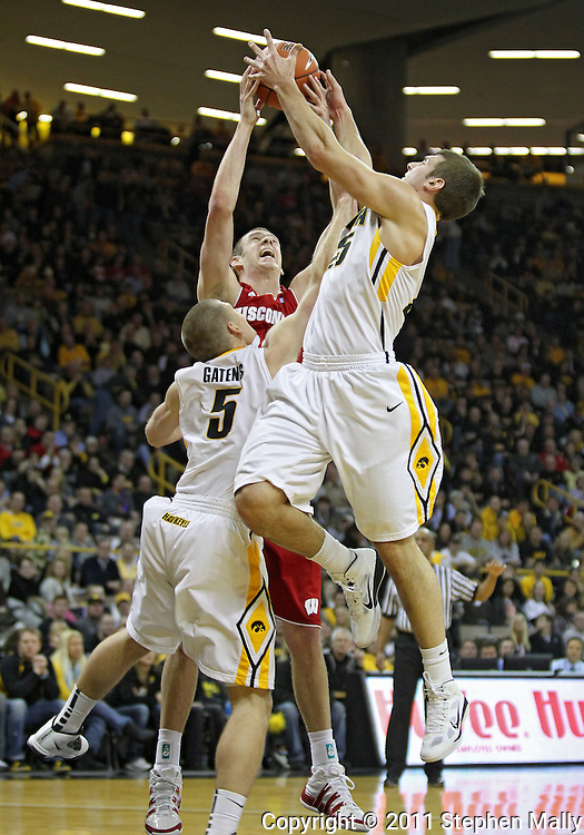 February 09 2011: Iowa Hawkeyes guard Matt Gatens (5), Wisconsin Badgers forward Jon Leuer (30), and Iowa Hawkeyes guard/forward Eric May (25) battle for a rebound during the first half of an NCAA college basketball game at Carver-Hawkeye Arena in Iowa City, Iowa on February 9, 2011. Wisconsin defeated Iowa 62-59.