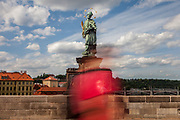 "A woman wearing a face-mask is passing the statue of  ""John of Nepomuk"" which is an outdoor sculpture, installed in 1683 on the north side of the Charles Bridge in Prague, Czech Republic. The Czech government lowered the security measures and as of Monday 25 May 2020, wearing of protective masks will be mandatory only in the interiors of buildings other than the place of residence and in public transport."