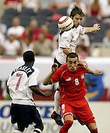 Team USA's Bobby Convey, top, lands on top of Poland's Ireneusz Jelen as Jelen heads the ball in a soccer game.at Soldier Field in Chicago.