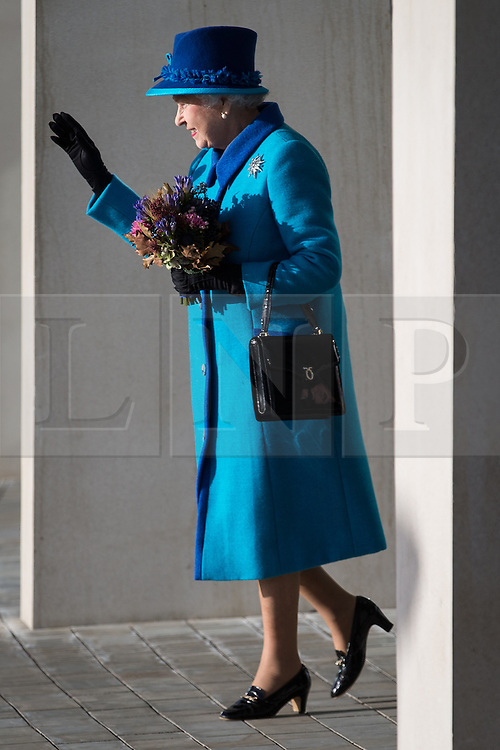 © Licensed to London News Pictures . 14/11/2013 . Manchester , UK . The Queen waves to crowds as she leaves . Queen Elizabeth II and the Duke of Edinburgh visit the Coop building at 1 Angel Square , Manchester , this morning ( 14th November 2013 ) . Photo credit : Joel Goodman/LNP