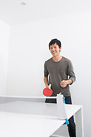 Happy mid adult man playing ping pong