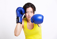 Portrait of young Asian woman wearing blue boxing gloves against white background