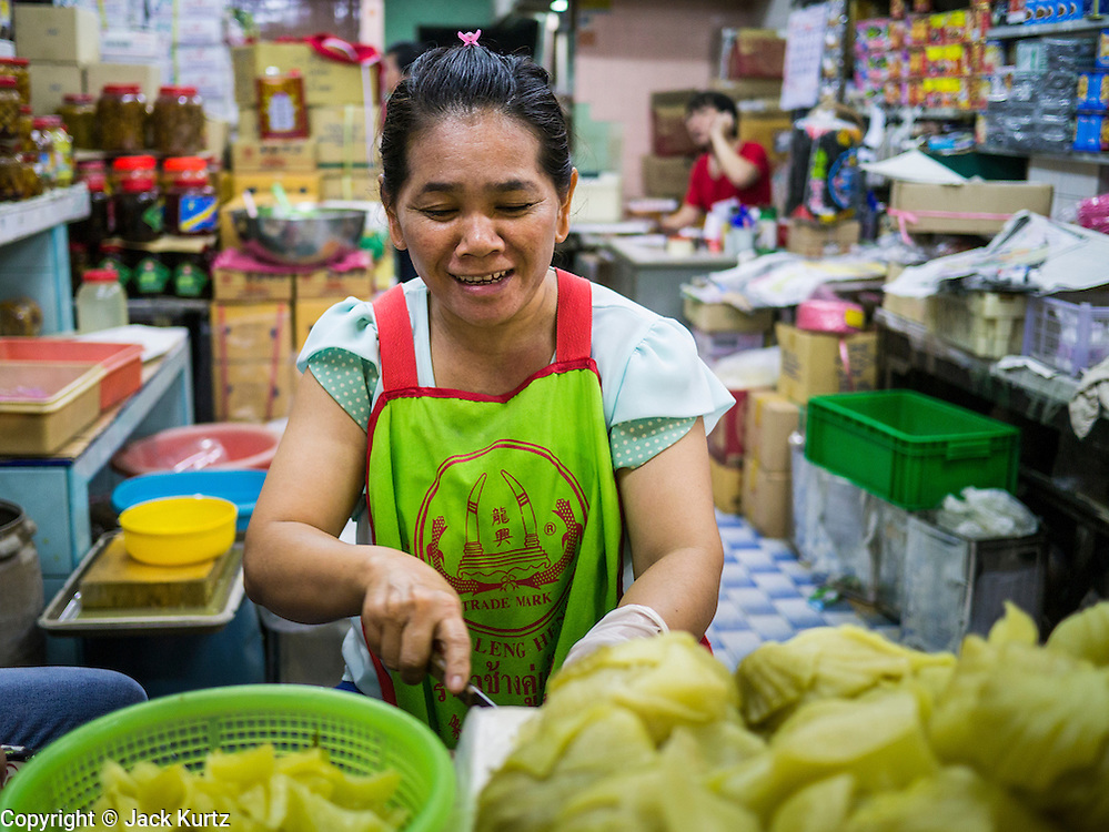 10 SEPTEMBER 2013 - BANGKOK, THAILAND:  A shop worker cuts up pickled cabbage in a shop in Chinatown.      PHOTO BY JACK KURTZ