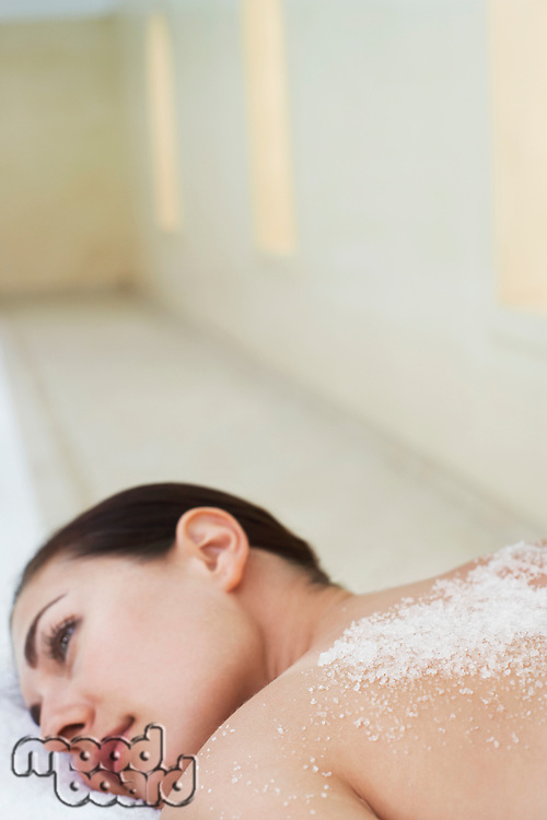 Young woman with salts on back lying on massage table portrait