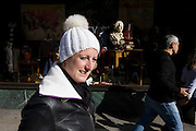 A womam wearing a bobble hat passes-by the a head of English playright William Shakespeare whose bust is in a London shop window