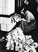 Hyperinflation in Germany post World War I:  Woman uses bank notes to fuel a stove.