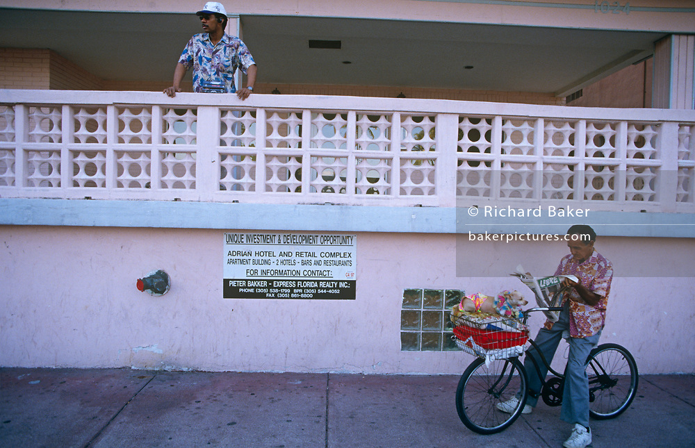 Local Latinos and a pink balcony of Art Deco architecture, on 15th May 1996, in Miami Beach, Florida, USA.