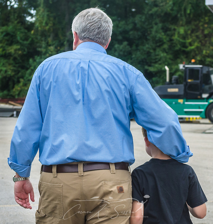 Pat Barber walks with his son, James, at Superior Transportation, Sept. 30, 2015, in North Charleston, South Carolina. Barber started the company in 1998. James, 6, is already showing a big interest in the company and its Mack trucks, and Barber says he hopes he will follow in his footsteps and carry on the family legacy.  (Photo by Carmen K. Sisson/Cloudybright)
