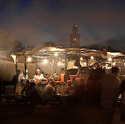 Restaurants in Djemma el Fna square and marketplace at night, Medina, Marrakech, Morocco. The minaret of the Koutoubia mosque can be seen in the background. Picture by Manuel Cohen