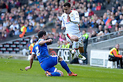 Brentford defender Maxime Colin slides in to tackle MK Dons forward (on loan from Norwich City) Josh Murphy during the Sky Bet Championship match between Milton Keynes Dons and Brentford at stadium:mk, Milton Keynes, England on 23 April 2016. Photo by Dennis Goodwin.