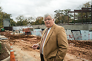 AUBURN, AL – NOVEMBER 20, 2016: Philip Dunlap walks in front of a mixed use development under construction in Auburn's urban core. The front part of the building facing the street will be rented by commercial tenants, and the rear will be an urban storage facility, which is attractive to small merchants in the area. Dunlap, the city of Auburn's Economic Development Director, worked for the city of Birmingham for nearly a decade until he was recruited by the city of Auburn in 1984 to start the city's Economic Development Program. Since that time, the city has witnessed significant growth and development.<br /> <br /> In much of the United States, global trade and technological innovation has failed to produce the prosperity hoped for by political and business leaders. Yet despite formidable economic challenges, some localities are flourishing. In Lee County, Ala., unemployment is below the national average despite the loss of thousands of manufacturing jobs, and the key to the county's resilience may be Auburn University, which provided a steady source of employment during recessions and helped draw new businesses to replace those that fled. CREDIT: Bob Miller for The Wall Street Journal<br /> [RESILIENT]