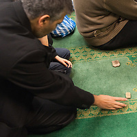 LONDON, ENGLAND - DECEMBER 27:  A Shia Muslim worshipper places on a carpet a piece of dry mud from Karbala before praying  inside Holland Park Mosque after the Ashura Procession on December 27, 2009 in London, England. Ashura is a 10 day period of mourning for Imam Hussein, the seven-century grandson of Prophet Mohammad who was killed in a battle in Karbala in Iraq, in 680 AD.  (Photo by Marco Secchi/Getty Images)