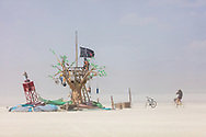 Island of Lost Buoys<br /> by: Lillian Heyward and The Island of Lost Buoys, a Create Change Project<br /> from: Bluffton, SC<br /> year: 2019<br /> <br /> On the playa is an Island, a wooden tree dominates the center made of recycled pallets, crates and drift wood. Leaves of sculpted plastic bottles rustle in the wind. Strung from a branch is a hammock made of fishing net attached to a ocean buoy marooned on the beach. Hanging from the branches are sea buoys and balls providing a place to write names or leave a message to those who will come after.<br /> <br /> Hanging from branches are bamboo wind chimes that softly clatter in the breeze. It is an island, a refuge, a place of calm and childhood in the stormy seas of life. It appears out of the playa as a mirage, the fantasy playground of youth. Discarded materials transform into an oasis, as our adult lives transform back to childhood. Bangarang!<br /> <br /> URL: http://www.createchangeproject.com<br /> Contact: islandoflostbuoys@gmail.com<br /> <br /> https://burningman.org/event/brc/2019-art-installations/?yyyy=&artType=B#a2I0V000001AVsTUAW