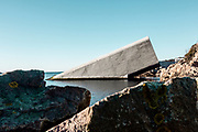 "Norway, Lindesnes Region, Under restaurant, the first underwater restaurant. Located at the southernmost point of the Norwegian coastline, where the sea storms from the north and south meet, the project is situated at a unique confluence. Marine species flourish here in the both briny and brackish waters to produce a natural abundance in biodiversity at the site. The Snøhetta-designed restaurant also functions as a research center for marine life, providing a tribute to the wild fauna of the sea and to the rocky coastline of Norway's southern tip.. In Norwegian, ""under"" has the dual meaning of ""below"" and ""wonder"". Half-sunken into the sea, the building's 34-meter long monolithic form breaks the surface of the water to rest directly on the seabed five meters below."