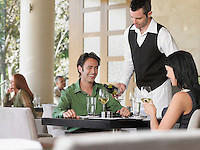 Waiter pouring wine for couple at outdoor restaurant