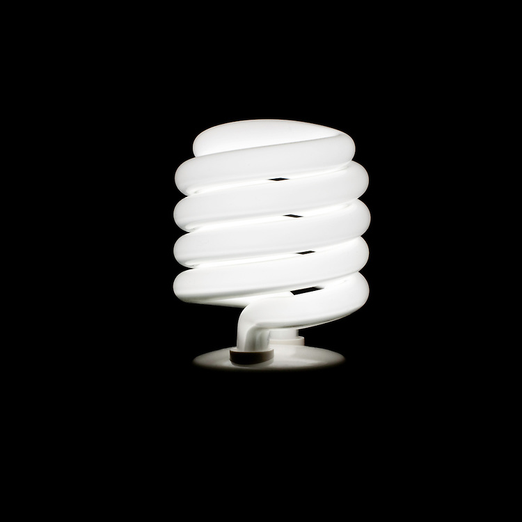 New York, New York - Fluorescent Light bulb illuminated against a black background.