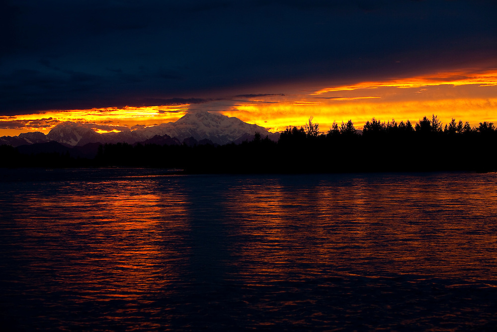 Alaska2010.-The sunset glows off of the Talkeetna River as it setys behind Denali the largest mountain in North America located in Denali National Park Alaska.