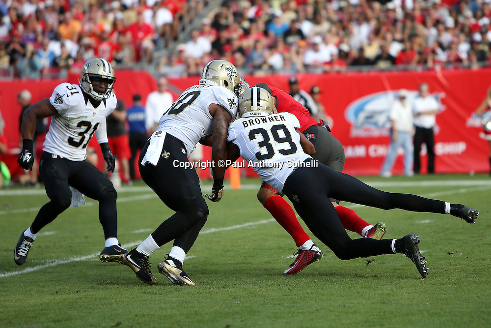 Tampa Bay Buccaneers wide receiver Mike Evans (13) gets gang tackled by New Orleans Saints cornerback Brandon Browner (39) and New Orleans Saints rookie middle linebacker Stephone Anthony (50) as he catches a 22 yard pass for a first down at the New Orleans Saints 28 yard line in the third quarter during the 2015 week 14 regular season NFL football game against the New Orleans Saints on Sunday, Dec. 13, 2015 in Tampa, Fla. The Saints won the game 24-17. (©Paul Anthony Spinelli)