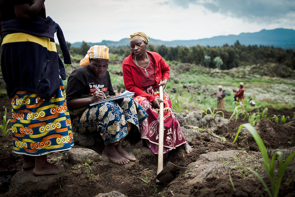 Women who form part of the co-operative Indatwailumurimu, take notes of who attended the harvest of Irish potatoes in the fields close to their village. Shingiro District, Rwanda