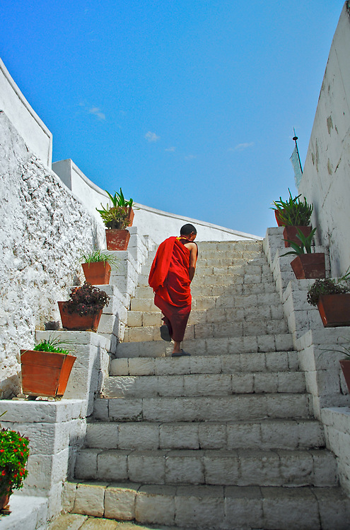 Monk ascending a staircase  within a monastery compound in Bhutan wearing traditional robes during summer with blue sky above