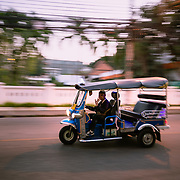 Panning shot of tuk tuk speeding along a local street in Chiang Mai