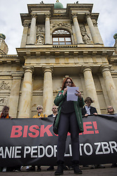 October 7, 2018 - Warsaw, Warsaw, Poland - Protester seen standing outside a church reading a testimony of a child who was molested by a priest during the protest..Hundreds of People Protest against children sexual violence from unpunished perpetrators in cassocks, bishops and the Catholic Church as an institution that for decades has tolerated the criminal activities of its employees and consistently refuse to disclose data of priests-criminals to the law enforcement agencies, they also read a list of cities and villages where clergymen molested children and published the map of church pedophilia. (Credit Image: © Attila Husejnow/SOPA Images via ZUMA Wire)