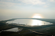 Nederland, Zuid-Holland, Rotterdam, 28-09-2014; De Slufter, grootschalige opslagplaats voor vervuild havenslib. De verontreinigde baggerspecie komt voort uit het onderhoudsbaggerwerk in de Rotterdamse haven waarbij de haven op diepte wordt gehouden. Langs de rand van de Slufter zijn windmolens gebouwd.<br /> The Slufter area in the South-West of the Netherlands, large-scale depot of contaminated harbor sludge from the Port of Rotterdam. Along the edge of the Slufter windmills are built.<br /> luchtfoto (toeslag op standard tarieven);<br /> aerial photo (additional fee required);<br /> copyright foto/photo Siebe Swart