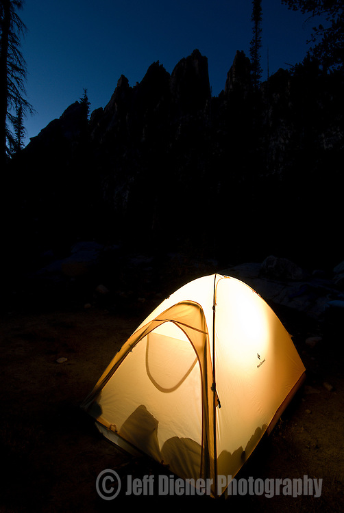 A tent glows below the Verita Ridge spires in the Sawtooth Mountains, Idaho.