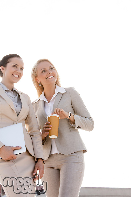 Young businesswomen with disposable cup and laptop looking away outdoors