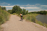 Woman biking the 89 mile Weiser River Trail, Idaho.