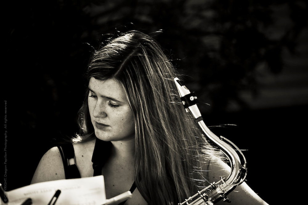 Candid photograph of young female saxophonist taking a break during an outdoor jazz performance.