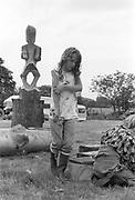 Girl standing by wooden sculpture, Glastonbury, Somerset, 1989
