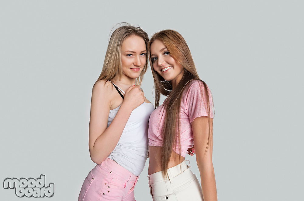 Portrait of smiling female friends against white background