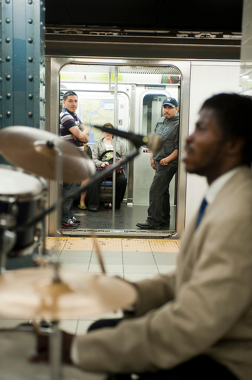 """Der """"Prinz von der 125ten Strasse"""" spielt seit vielen Jahren fast jeden Tag an der gleichen Stelle unter Harlems Hauptstrasse auf der Nr. 6 Ubahn Plattform. Oft halten durchreisende Rap Saenger an um ein zwei Lieder mit ihm zu singen...Jedes Jahr im Mai laden die Betreiber der New Yorker Subway (MTA) ca 60 Musiker und Gruppen zu einem Wettberwerb im Grand Central Station ein. Die Gewinner duerfen ganz legal an ihnen zugeteilten Orten im Ubahn System auftreten. Viele unangemeldete  und selbst organisierte Musiker jeder nur erdenklichen Musikrichtung spielen zudem in fast jeder wichtigen Ubahnstation. Die Angst vor der Polizei ist dabei gering, selten gibt es eine Verwarnung und noch seltener ein Bussgeld. Meist wird einfach der Ort gewechselt falls es Probleme gibt...He calls himself the """"The Prince of 125th Street"""" and his drumming can be heard almost every day at the same spot on the Nr. 6 train under 125th street in Harlem. Often he gets joined by visiting rap singers for a song or two...MTA (Metropolitan Transportation Authority) .Music Under New York.Auditions.Every Spring, Music Under New York (MUNY) presents a day of auditions in Grand Central Terminal to review and add new performers to the MUNY roster. This year, MUNY held its annual auditions in May on the Northeast Balcony of the Grand Central Terminal. .In addition legions of non-official musicians play in New Yorks subway stations and on platforms. One can find every thinkable style and instrument underground. ..Foto: Stefan Falke."""