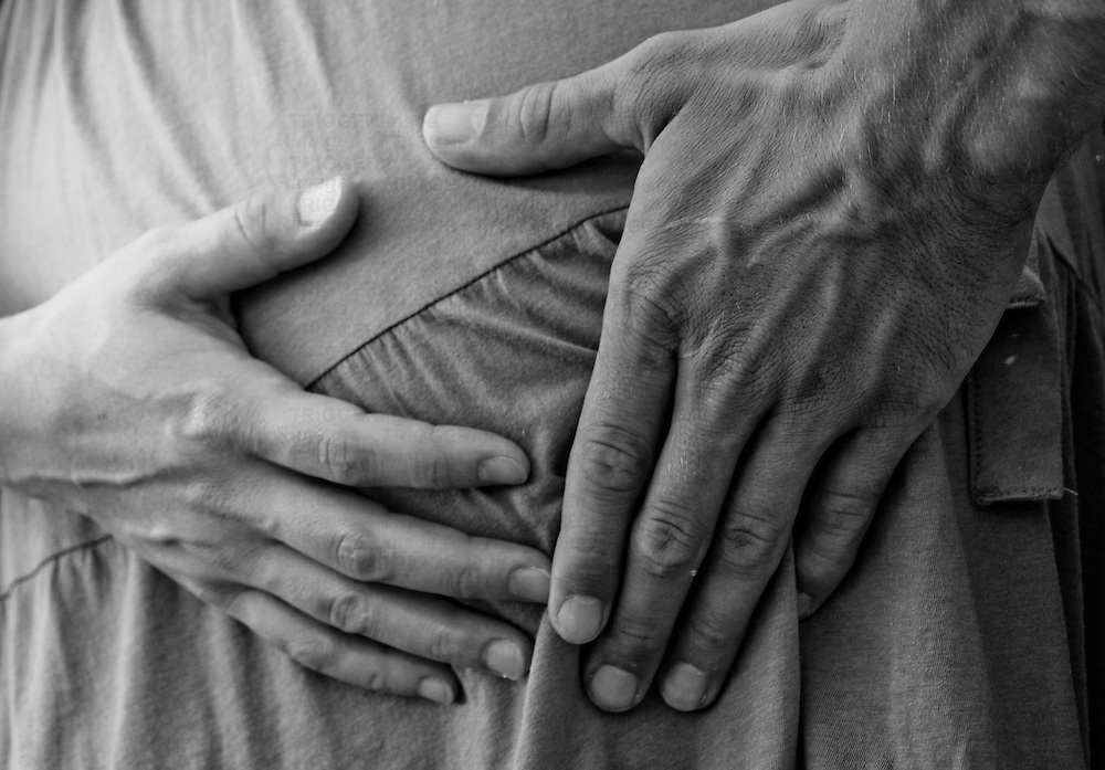 close up detail of a man and woman's hands on a belly.