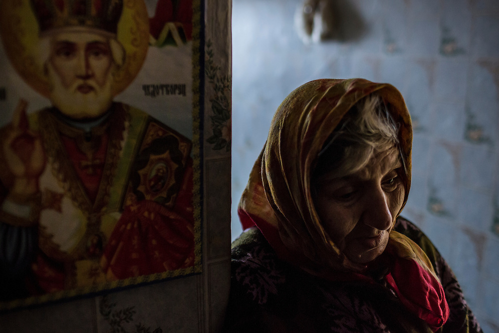 KOMUNAR, UKRAINE - JANUARY 27, 2015: Valentina Mozschagina, 80, who can afford to eat only porridge, at her home in Komunar, Ukraine. Mozschagina is the only caregiver for her disabled son Viktor, 58. CREDIT: Brendan Hoffman for The New York Times