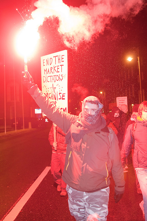 A masked man leads the protesters to Merrion Street in Dublin, Ireland, on 7/12/2010.