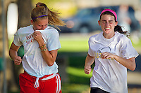 Samantha Kirkendall, left, wipes ash aphids from her face while running alongside her soccer teammate Whitney Gerleman during a practice run through City Park Wednesday.