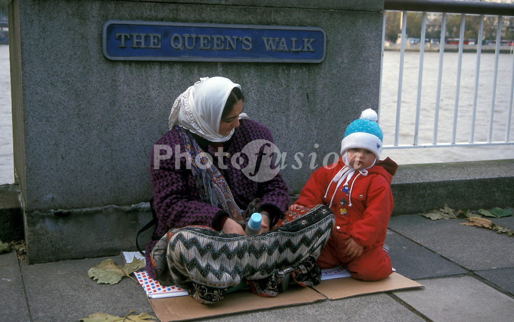 Woman begging with child London Embankment UK