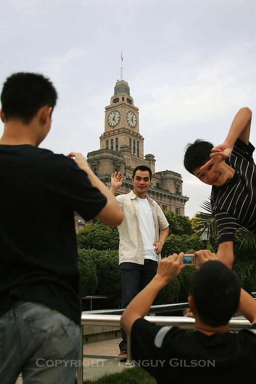 Young Chinese tourists posing goofing around on the Bund in Shanghai, China