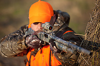 DEER HUNTER WITH A MOSSBERG SHOTGUN AND WEARING BLAZE ORANGE AND REALTREE CAMOUFLAGE SHOOTING FROM BEHIND HAY BALES