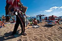 Salento - Puglia - Marina di Pescoluse - Extracomunitario percorre la spiaggia per vendere la propria merce.