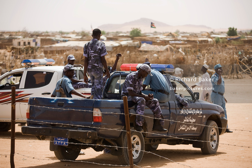 Sudanese police stand guard during a visit by a western delegration to the 4 sq km Abu Shouk refugee camp, which is (disputedly) home to 38,000 displaced persons, on the outskirts of Al Fasher, North Darfur, Sudan.